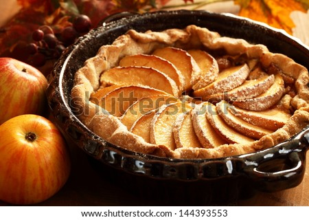 Arrangement of home-made apple pie and apples. - stock photo