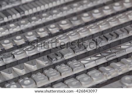 Arrangement of letterpress lead letters in row - stock photo