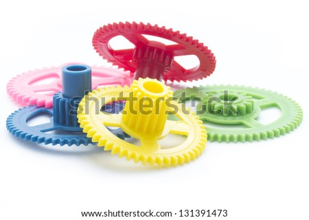arrangement of multicolor plastic cog gear isolated on white - stock photo