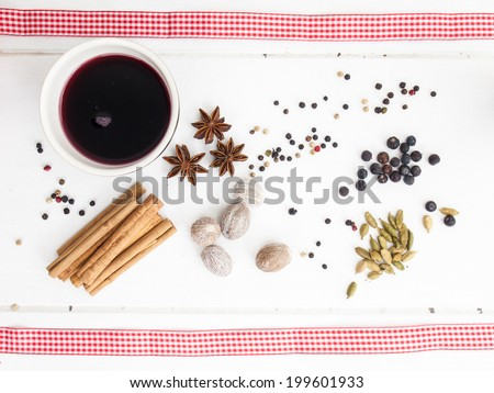 arrangement of  nutmeg and cinnamon with red ribbon on a rustic, aged, white wooden table top - stock photo