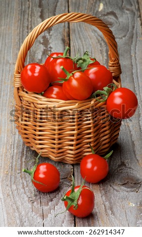 Arrangement of Perfect Ripe Cherry Tomatoes with Stems in Wicker Basket isolated on Rustic Wooden background - stock photo