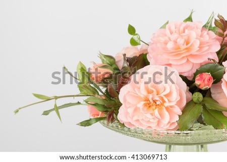Arrangement of pink garden roses in green glass vase, close up with copy space - stock photo