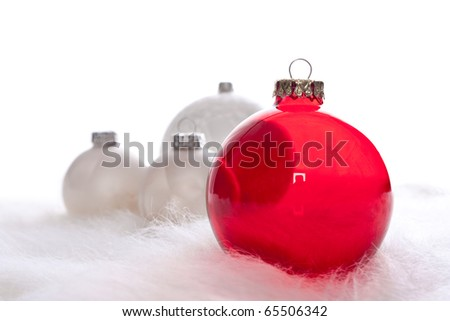 Arrangement of red and some white christmas baubles on white fur - stock photo