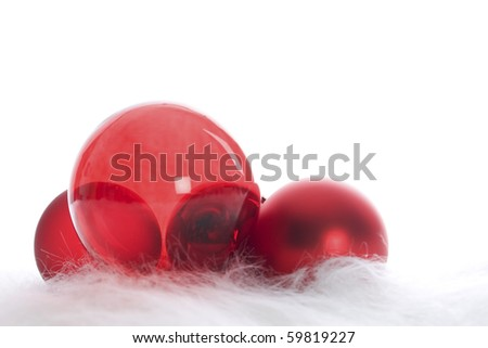 Arrangement of red Christmas baubles on white fur - stock photo
