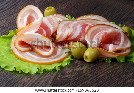 Arrangement of Smoked Ham Slices with Green Olives and Lettuce closeup on Dark Wooden background - stock photo