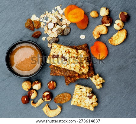 Arrangement of Useful Granola Bars with Muesli, Nuts, Dried Apricots and Bowl of Honey closeup on Black Stone background. Top View - stock photo