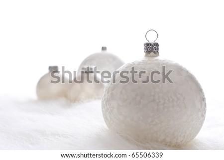 Arrangement of white christmas baubles on white fur - stock photo