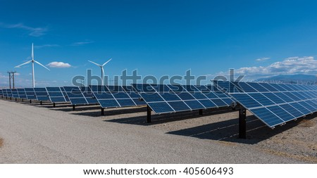 Arrays of solar panels and rows of wind turbines capture energy - stock photo
