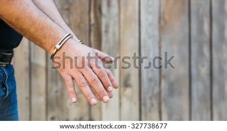 Arrest, close-up shot man's hands with handcuffs in front of plank wood  wall with copy-space - stock photo