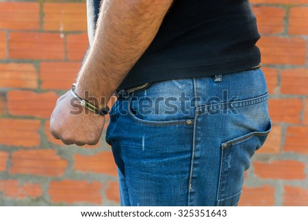 Arrest, close-up shot man's hands with handcuffs in front of terracotta brick blocks wall, left hand side - stock photo