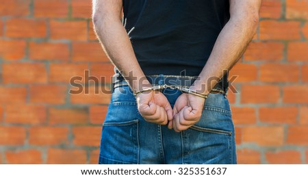 Arrest, close-up shot man's hands with handcuffs in front of terracotta brick blocks wall with copy-space - stock photo
