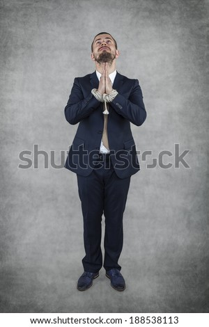 Arrested businessman praying - stock photo