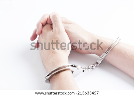 Arrested criminal hands in handcuffs - stock photo