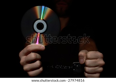 Arrested hacker holding computer disk - stock photo