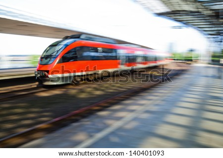 arriving train in a railway station with intentional motion blur - stock photo