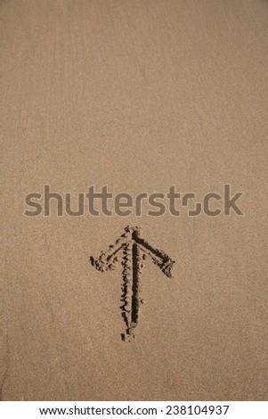 arrow drawn on brown sand ground low tide beach ocean seashore in Spain Europe - stock photo