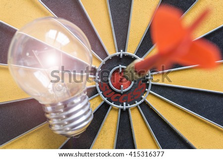 Arrow hitting the success bullseye target with idea lamp on dartboard, Success business finance investment concept, symbol of successful - stock photo