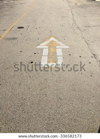Arrow sign on the road to go toward - stock photo