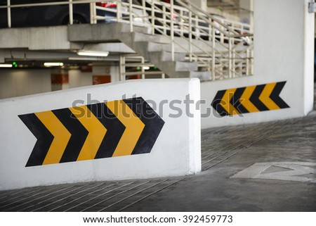 Arrows point the way inside of a city parking structure - stock photo