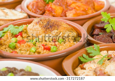 Arroz Con Pollo - Chicken and rice cooked with sofrito and beer. Surrounded by other tapas dishes. - stock photo