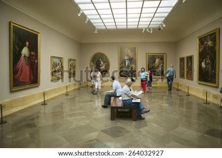 Art appreciators view paintings in Museum de Prado, Prado Museum, Madrid, Spain - stock photo