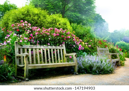 Art bench and flowers in the morning in an English park - stock photo