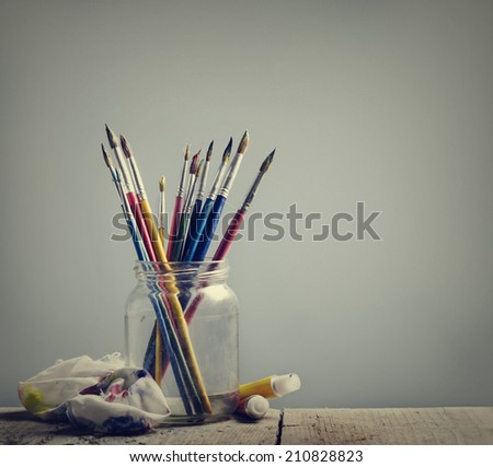 Art brushes and colors on wooden table - stock photo