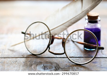 Art concept. Closeup of old spectacles near quill and ink-pot on wooden table - stock photo