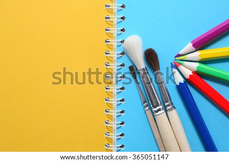 Art concept. Colored pencils and paintbrushes on notebook with blank pages - stock photo