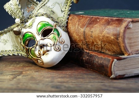 Art concept. Vintage still life with old books near Venetian mask - stock photo