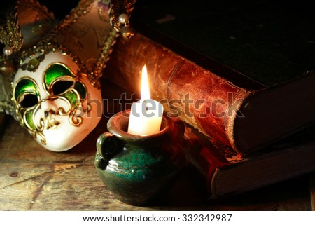 Art concept. Vintage still life with old books near Venetian mask and lighting candle - stock photo