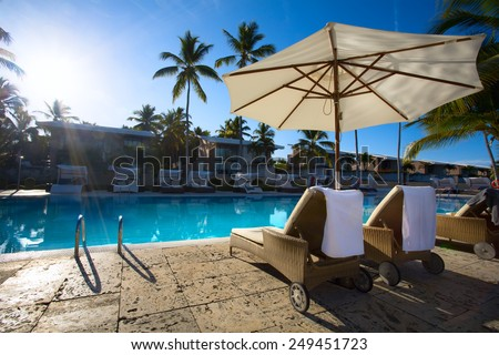 art Deckchairs in tropical resort hotel pool - stock photo