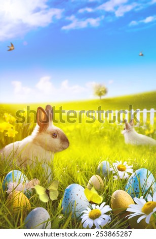 Art Easter bunny and easter eggs on field - stock photo