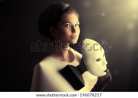 Art fashion photo of a gorgeous woman in paper dress holding theatrical mask. Black and white. - stock photo