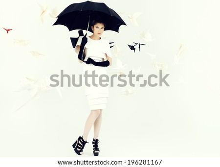 Art fashion photo of a gorgeous woman in paper dress holding umbrella. Black and white. - stock photo