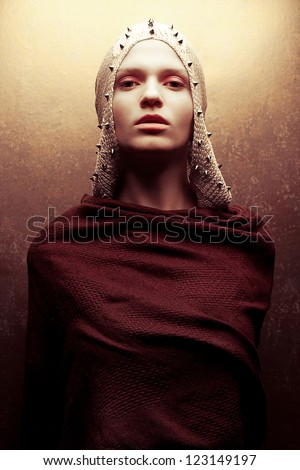Art-fashion portrait of a glamorous queen-warrior in golden cape with golden pricks. Studio shot - stock photo