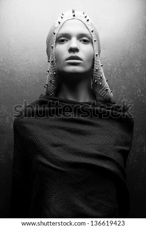 Art-fashion portrait of a glamorous queen-warrior in vintage cape with silver pricks. Black and white (monochrome) studio shot - stock photo
