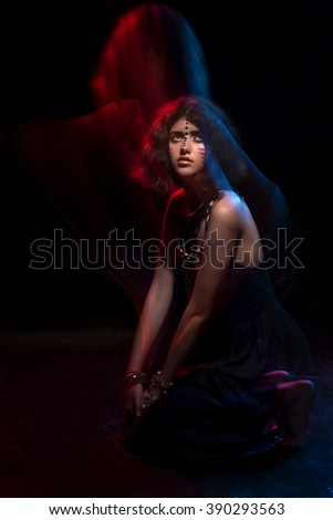 Art fashion portrait of beautiful young woman girl with tribal creative face art make up in mixed light on studio. Mixed light photography techniques, colored spotlights, low key. Ethnic style. - stock photo