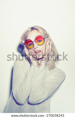 Art fashion woman portrait. color red Sunglasses Hippi blond  hair white sweater emotional posing. make funny face. - stock photo