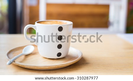 Art Latte Coffee in a cup on wooden table. - stock photo