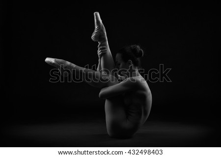 Art nude. Perfect flexible sexy body of young woman on black background. Studio shot - stock photo