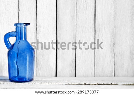 Art of Still Life Transparent Blue Indigo Vase on White Wooden Table and Wall - Abstract Texture Background - stock photo