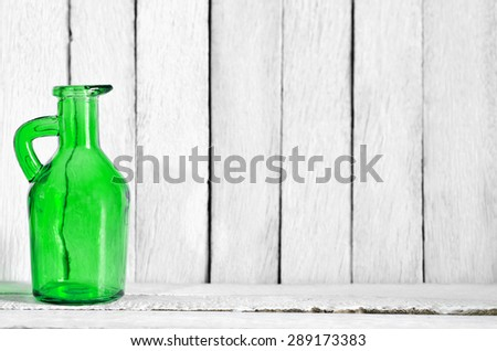 Art of Still Life Transparent Dark Green Vase on White Wooden Table and Wall - Abstract Texture Background - stock photo