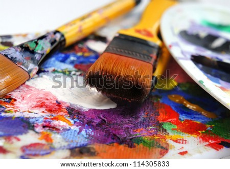Art palette and brushes with a lot of colors - stock photo