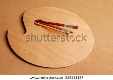 Art palette and paintbrushes. - stock photo