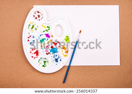 Art palette with blank paper and brush for watercolor drawing - stock photo