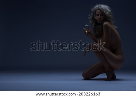 Art photo of naked blonde with fragrance.  Naked woman with glossy skin holding perfume. Long shiny blond hair. Cosmetics concept.Toned in warm colors. Shot in studio, horizontal. - stock photo