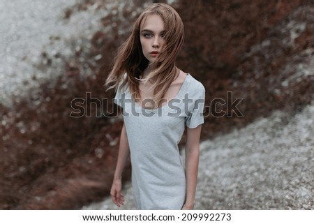 Art portrait of a beautiful fashion girl in the wind on a cloudy day - stock photo