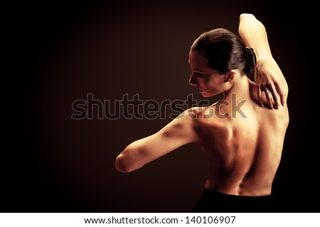 Art portrait of a beautiful  woman back over black background. - stock photo