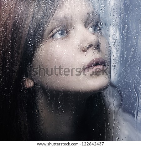 Art portrait of a beautiful young sadly girl standing at the window watching the rain - stock photo
